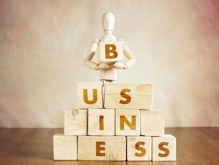 marioneta de madera: El hombre de negocios construye su propio negocio. Imagen conceptual con la marioneta de madera