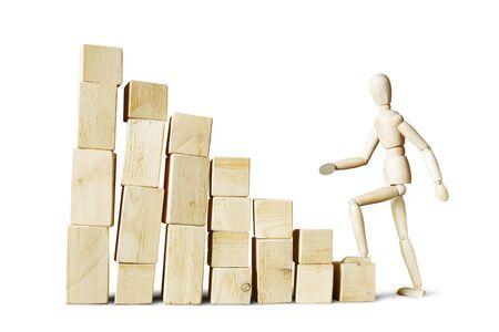 marioneta de madera: Hombre que sube hasta alta pila de bloques. Imagen abstracta con una marioneta de madera