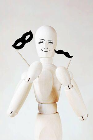 wooden puppet: El hombre sostiene la mascara y bigote falso. Imagen abstracta con una marioneta de madera Foto de archivo