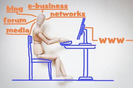 marioneta de madera: El hombre trabaja con su ordenador en internet. Imagen abstracta con una marioneta de madera Foto de archivo