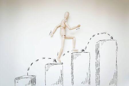 marioneta de madera: El hombre que salta más arriba, paso a paso. Imagen abstracta con una marioneta de madera Foto de archivo