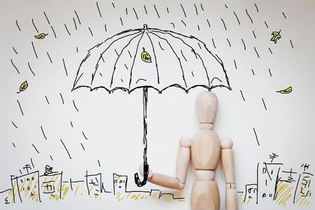 marioneta de madera: Hombre que se coloca bajo el paraguas en lluvia. Imagen abstracta con una marioneta de madera