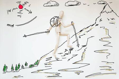 marioneta de madera: El hombre trepando a la alta montaña. Imagen abstracta con una marioneta de madera