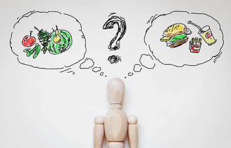 puppet: Man choosing healthy food. Abstract image with wooden puppet Stock Photo
