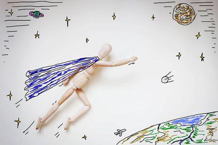 marioneta de madera: Superh�roe volando en el espacio sobre el mundo. Imagen abstracta con una marioneta de madera