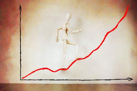 marioneta de madera: El empresario va arriba en el gráfico de levantamiento. Imagen abstracta con una marioneta de madera