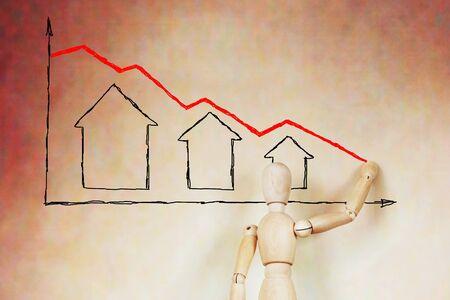 wooden puppet: El hombre se representa el gr�fico de la ca�da de los precios de bienes ra�ces. Imagen abstracta con una marioneta de madera