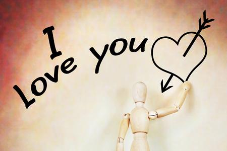 wooden puppet: Hombre escribe Te amo y dibuja el coraz�n con una flecha. Imagen abstracta con una marioneta de madera