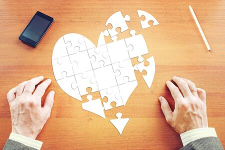 unfortunate: Man collects a heart as puzzles on the desk. Abstract image with paper scrapbooking