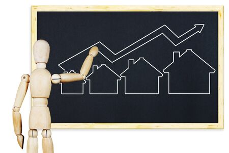 indices: Man draws a graph of real estate sales growth on a blackboard. Abstract image with wooden puppet Stock Photo