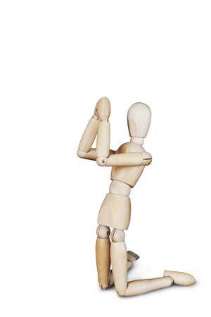 wooden puppet: Hombre de oraci�n en las rodillas aisladas sobre blanco. Imagen abstracta con una marioneta de madera