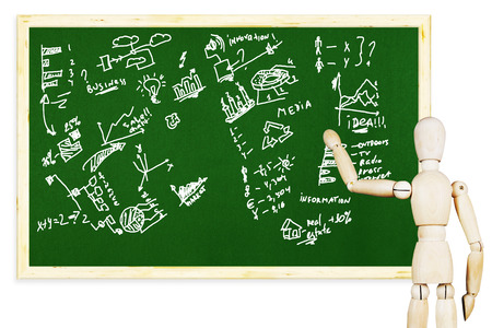 marioneta de madera: Man draws various graphs and charts on the green chalkboard. Abstract image with a wooden puppet
