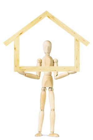 wooden puppet: El hombre sostiene el modelo de la casa aislado sobre fondo blanco. Imagen abstracta con una marioneta de madera