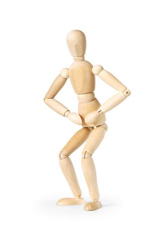 marioneta de madera: Hombre haciendo sentadillas mientras que los ejercicios de la mañana aisladas sobre fondo blanco. Imagen abstracta con una marioneta de madera Foto de archivo