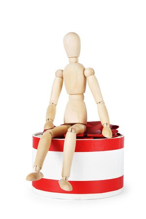 marioneta de madera: Man sits on the huge round gift box. Abstract image with a wooden puppet Foto de archivo