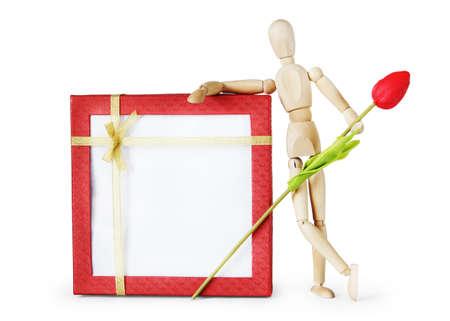 marioneta de madera: El hombre se coloca al lado de caja de regalo enorme y mantiene la flor del tulipán. Imagen abstracta con una marioneta de madera