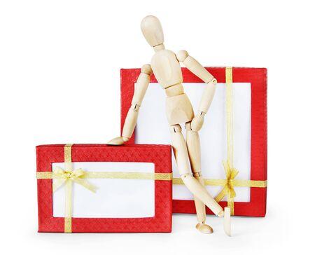 marioneta de madera: El hombre se coloca al lado de dos grandes cajas de regalo. Imagen abstracta con una marioneta de madera