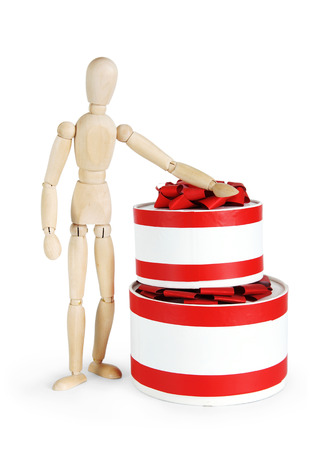 marioneta de madera: Man stands next to two huge round gift boxes. Abstract image with a wooden puppet Foto de archivo