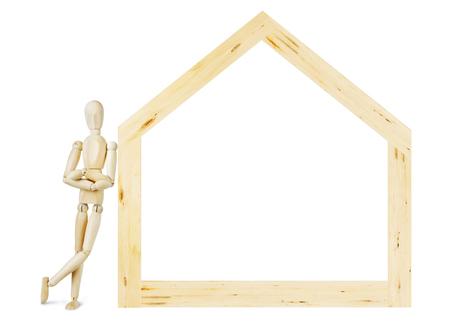 marioneta de madera: El hombre se apoy� en el modelo de casa de madera. Imagen abstracta con una marioneta de madera Foto de archivo