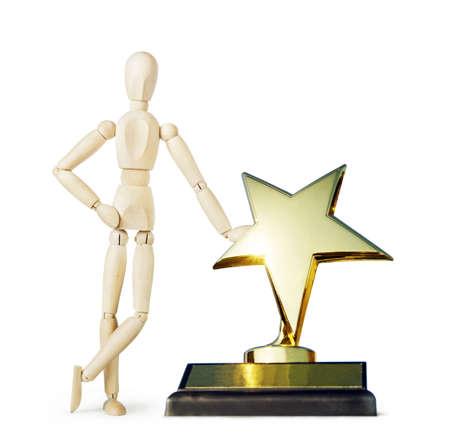 wooden puppet: El hombre se coloca cerca del gran premio estrella de oro. Imagen abstracta con una marioneta de madera