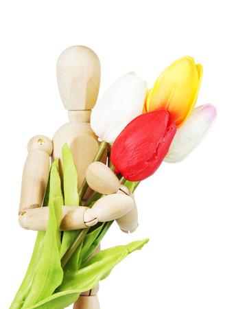 marioneta de madera: Hombre con un ramo de flores. Imagen abstracta con una marioneta de madera y tulipanes artificiales