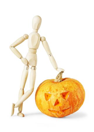 marioneta de madera: El hombre se apoy� en un gigante de la calabaza de Halloween. Imagen abstracta con una marioneta de madera Foto de archivo