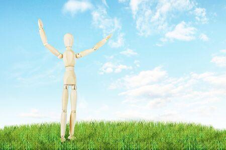 wooden puppet: hombre feliz se coloca en el c�sped verde al aire libre. Imagen abstracta con una marioneta de madera