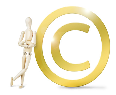 leaned: Man leaned against a huge golden Copyright sign. Abstract image with a wooden puppet Stock Photo