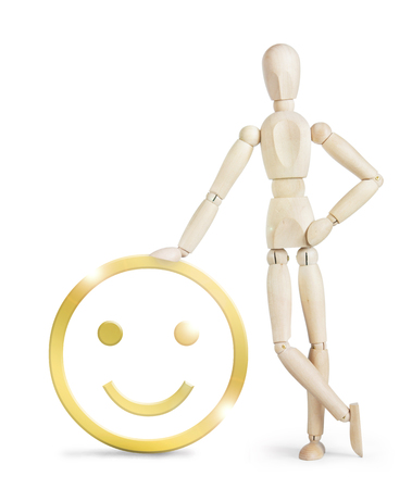 leaned: Man leaned against a large golden positive smiley. Abstract image with a wooden puppet Stock Photo