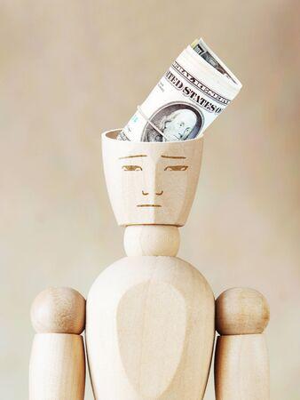 marioneta de madera: Manojo de dólares en la cabeza humana. Imagen abstracta con una marioneta de madera