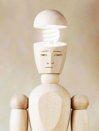 marioneta de madera: Bombilla de luz en la cabeza humana. Concepto de genio. Imagen abstracta con una marioneta de madera