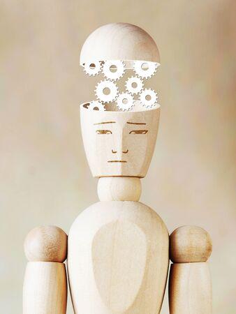 marioneta de madera: Muchas ruedas dentadas de trabajo dentro de la cabeza humana. Imagen abstracta con una marioneta de madera