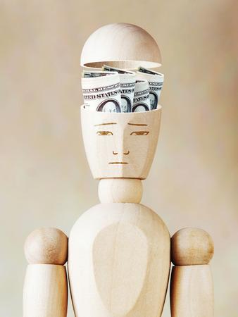 marioneta de madera: Muchos billetes de dólares se encuentran en la cabeza humana. Imagen abstracta con una marioneta de madera Foto de archivo