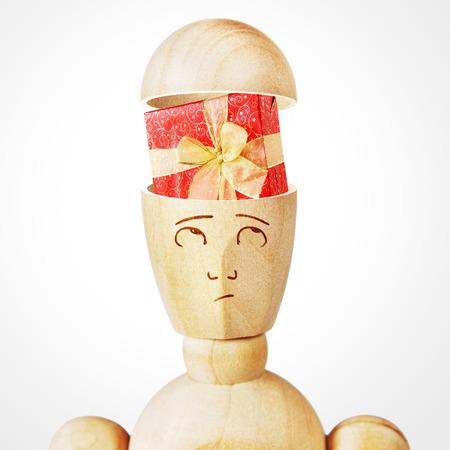 marioneta de madera: Caja de regalo en la cabeza humana. Imagen abstracta con una marioneta de madera Foto de archivo