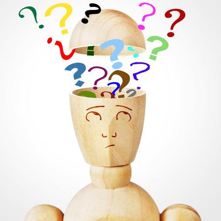 marioneta de madera: Muchos signos de interrogación en la cabeza humana. Imagen abstracta con una marioneta de madera