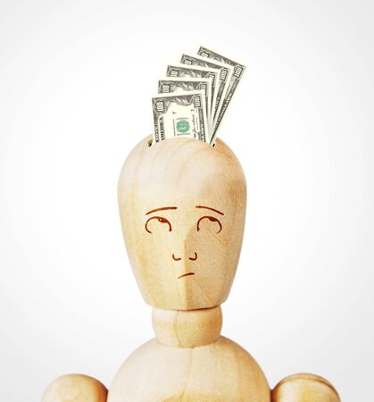brainpan: Many dollar banknotes are inserted into a human head as into a money box. Abstract image with a wooden puppet