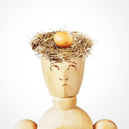 marioneta de madera: nido de pájaro con un huevo en la cabeza del hombre. Imagen abstracta con una marioneta de madera