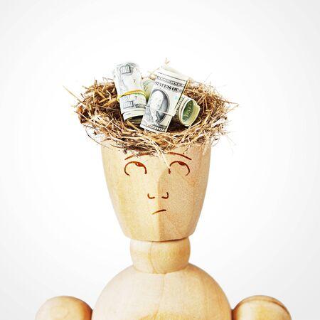 marioneta de madera: nido de p�jaro con billetes de d�lares americanos en una cabeza del hombre. Imagen abstracta con una marioneta de madera