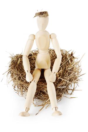 marioneta de madera: El hombre se sienta en el nido de pájaro. Imagen abstracta con una marioneta de madera