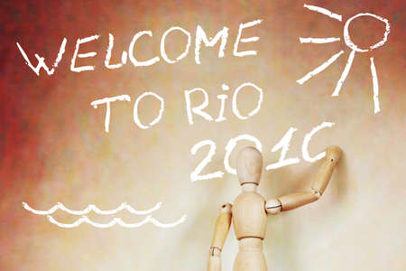 marioneta de madera: Man writing text Welcome to Rio 2016. Abstract conceptual image with a wooden puppet