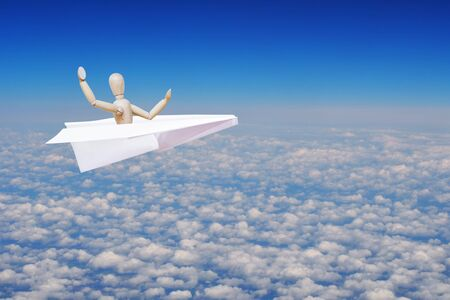 flying man: Man flying high over clouds in the toy paper plane