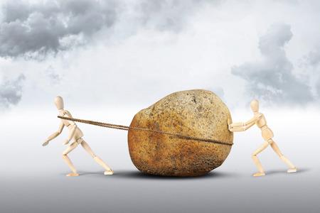 pull toy: Dos hombres se mueven una enorme piedra. Imagen abstracta con muñecos de madera Foto de archivo