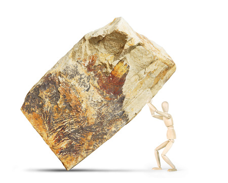 marioneta de madera: Man lifts up a huge rock. Abstract image with a wooden puppet