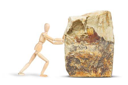 marioneta de madera: El hombre trata de mover una gran roca. Imagen abstracta con una marioneta de madera Foto de archivo