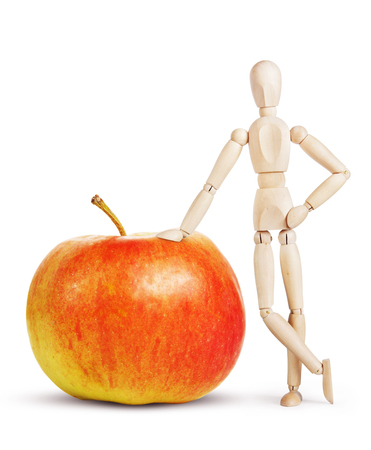 marioneta de madera: Man leans on a huge red apple. Abstract image with a wooden puppet Foto de archivo