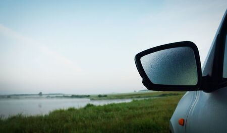 rear view mirror: Morning landscape at the lake shore with misted rear view mirror of a car