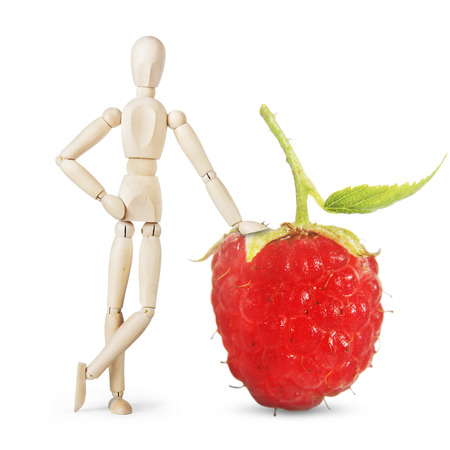 lean out: Man leans on a huge ripe raspberry. Abstract image with a wooden puppet