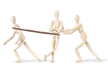 slacker: Two people pull another one to make him move. Abstract image with wooden puppets Stock Photo