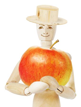 marioneta de madera: Jardinero tiene una gran manzana roja. Imagen abstracta con una marioneta de madera Foto de archivo