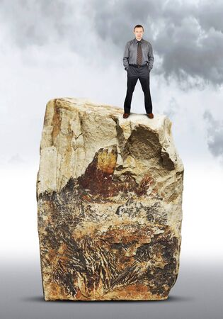 Assertive man stands on the top of a huge rock Stock Photo
